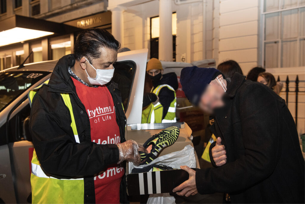 andrew-faris-offering- gift-to-homeless-person